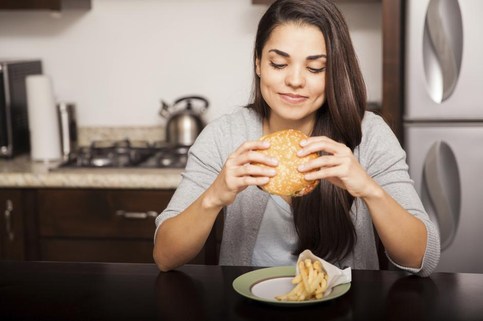 Žena jede hamburger | Author: Thinkstock