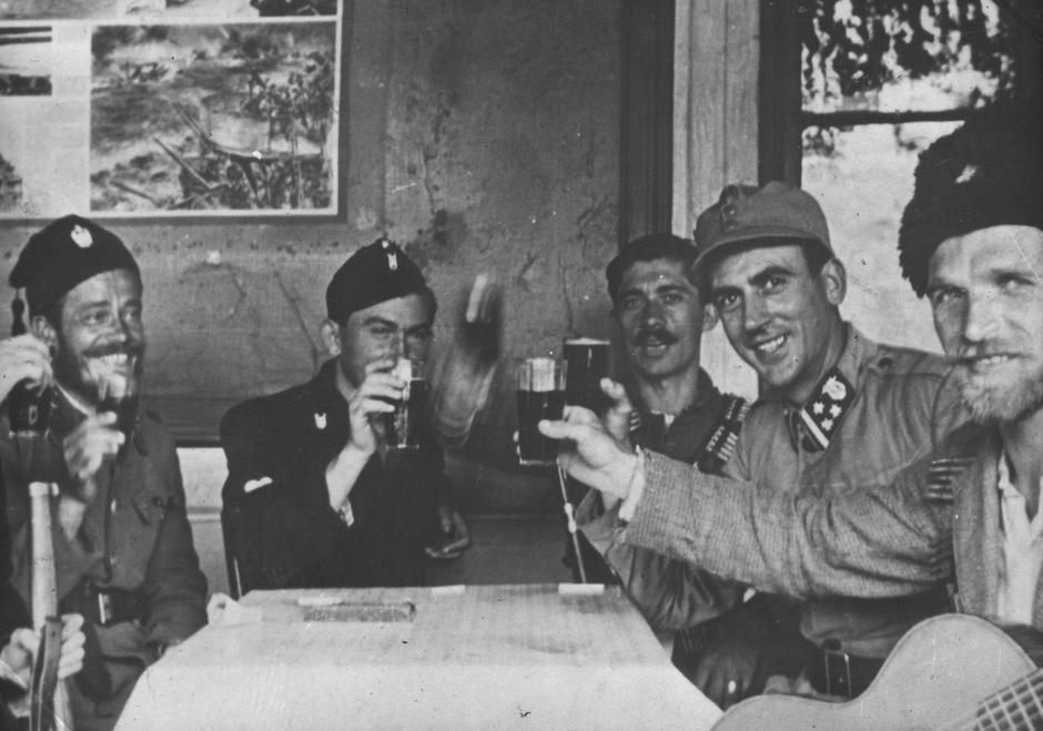 Četnici, narednik Domobranstva NDH i Ustaške vojnice nazdravljaju oko 1942. (Lijevo, sa šubarom, Uroš Drenović) | Author: Wikipedia